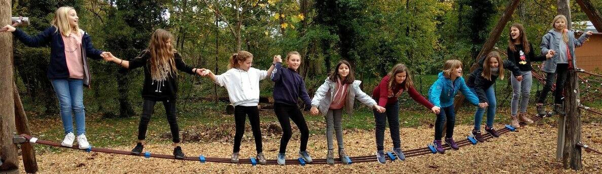 Kinder stehen gemeinsam auf einem schmalen Seil